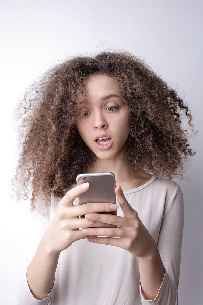 surprised young woman browsing mobile phone
